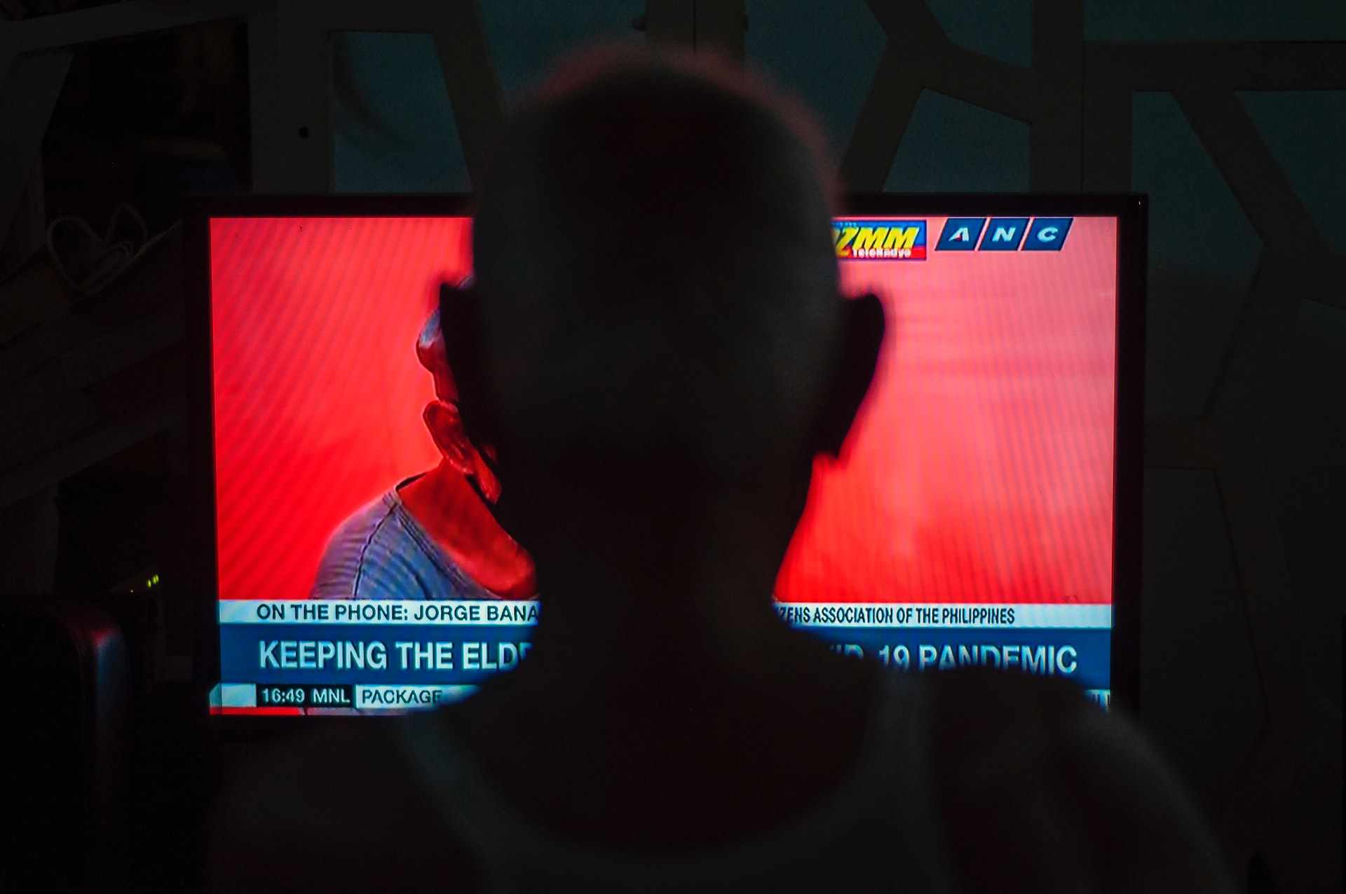 An old man watching the news