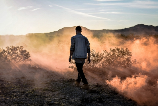 A man dressed in a jean jacket and boots walks through a desert.