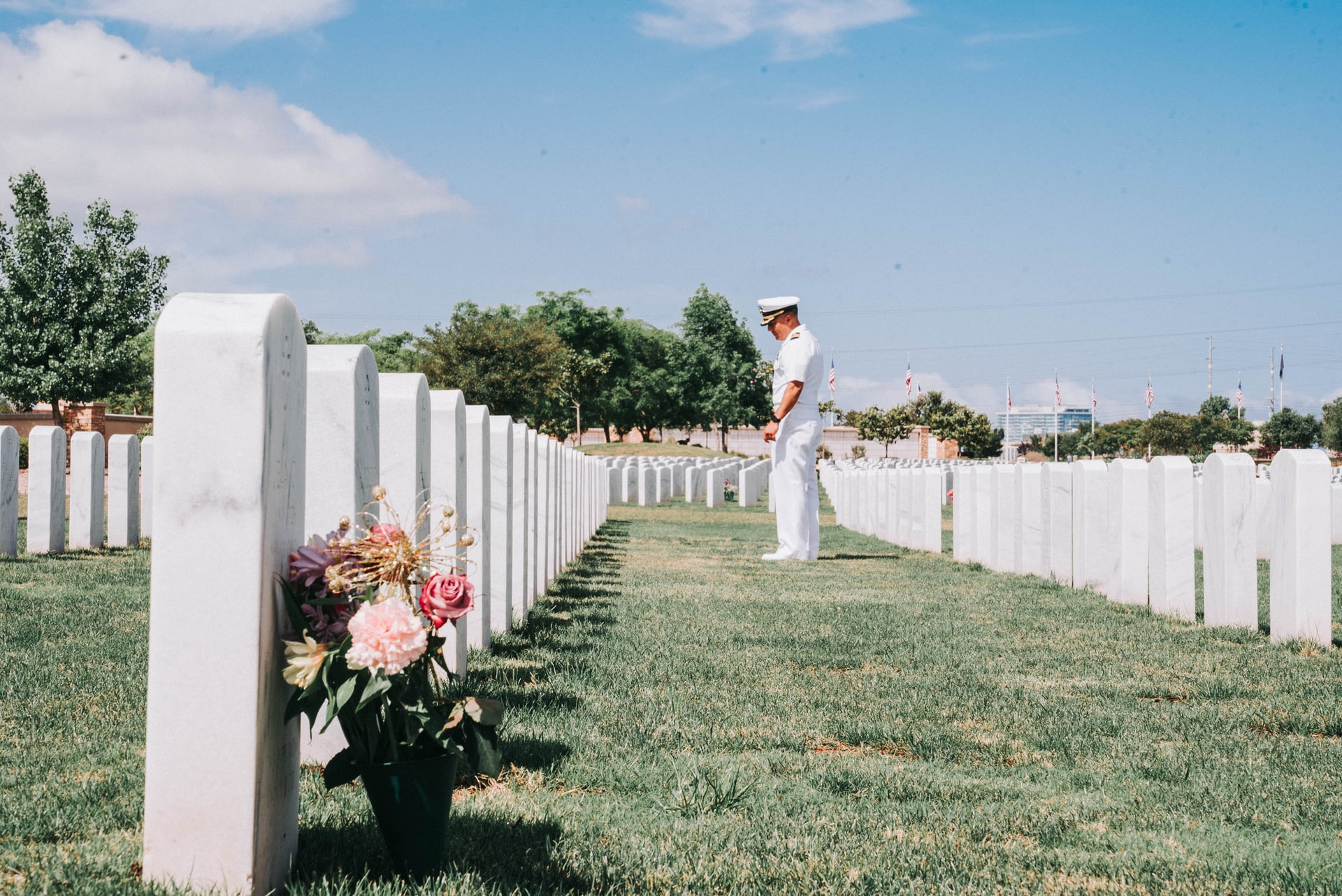 A soldier in dress whites stands among tombstones.